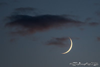 Young moon under cloud